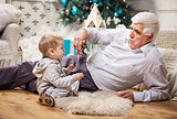 Toddler boy and his grandpa playing with toy dinosaur at Christmas tree