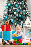 Cute toddler boy playing with building blocks at Christmas tree