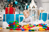 Cute toddler boy sitting at Christmas tree and reading book. Building blocks scattered around.