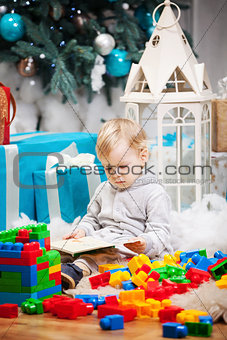 Cute toddler boy sitting at Christmas tree and reading book