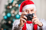 Senior man taking photo on Christmas background