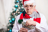 Senior man with money on Christmas background