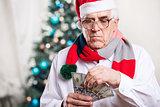 Senior man with money on Christmas background