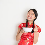 Asian chinese girl eating and looking up