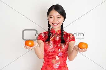 Asian chinese girl holding tangerine