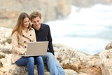 Couple sharing a laptop on the beach on holidays