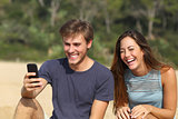 Funny man and woman laughing watching the smart phone