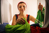 Woman Doing Housekeeping Taking Dry Clothes From Dryer At Home