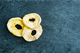 Closeup on dried apple slices on stone substrate