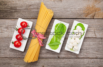 Tomatoes, mozzarella, pasta and green salad leaves