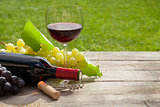 Red wine glass and bottle with bunch of grapes