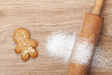 Rolling pin with flour and gingerbread cookie on wooden table