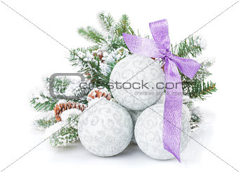 Christmas baubles and purple ribbon with snow fir tree