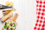 Fresh healthy salad and condiments over white wooden table