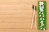 Chopsticks and sakura branch over bamboo mat