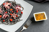 Pasta with black cuttlefish ink and small octopuses