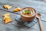 A bowl of hummus with corn chips