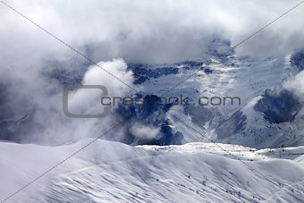 Off-piste slope in sunlight clouds