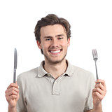 Young happy man holding a fork and a knife
