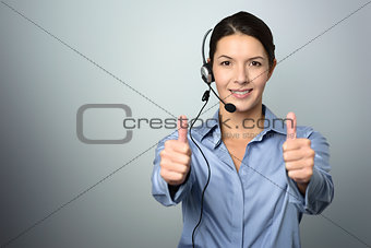 Attractive call center operator giving thumbs up
