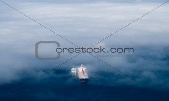 Cargo ships emerging from fog