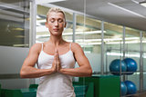 Woman with joined hands and eyes closed at fitness studio