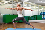 Fit woman doing stretching exercise in gym