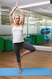 Sporty woman standing in tree pose at fitness studio
