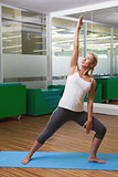 Fit young woman doing stretching exercise in gym