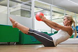 Side view of woman in boat pose at fitness studio