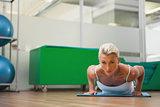 Beautiful woman doing push ups in in fitness studio