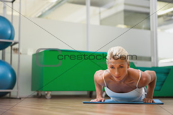Beautiful woman doing push ups in in fitness studio