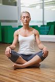 Sporty woman sitting with eyes closed in fitness studio