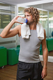 Handsome man drinking water at gym