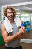 Smiling handsome man holding water bottle at gym