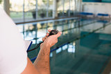 Cropped swimming coach with stopwatch by pool at leisure center