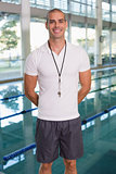 Swimming coach by pool smiling at leisure center