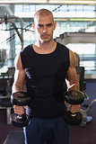 Man exercising with dumbbells in gym