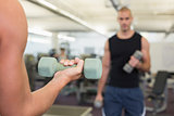 Blurred man exercising with dumbbell in gym