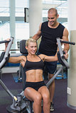 Trainer assisting woman on fitness machine at gym