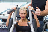Fit woman using fitness machine at gym