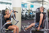 Fit young couple using fitness machines at gym