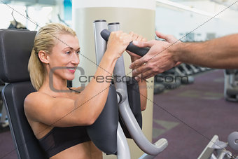 Fit young woman using fitness machine at gym