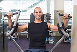 Smiling man working on fitness machine at gym