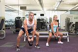 Fit couple lifting kettle bells in gym