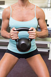 Mid section of a woman lifting kettle bell in gym