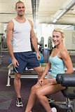 Fit smiling young couple in gym