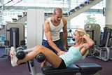 Male trainer assisting woman with abdominal crunches at gym