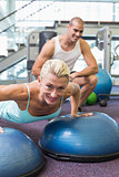 Trainer assisting woman with push ups at gym
