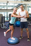Trainer assisting woman with stretching exercises at gym
